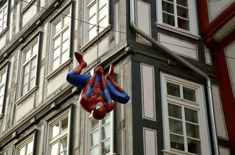 Spiderman Hanging Upside Down in Front of a Building