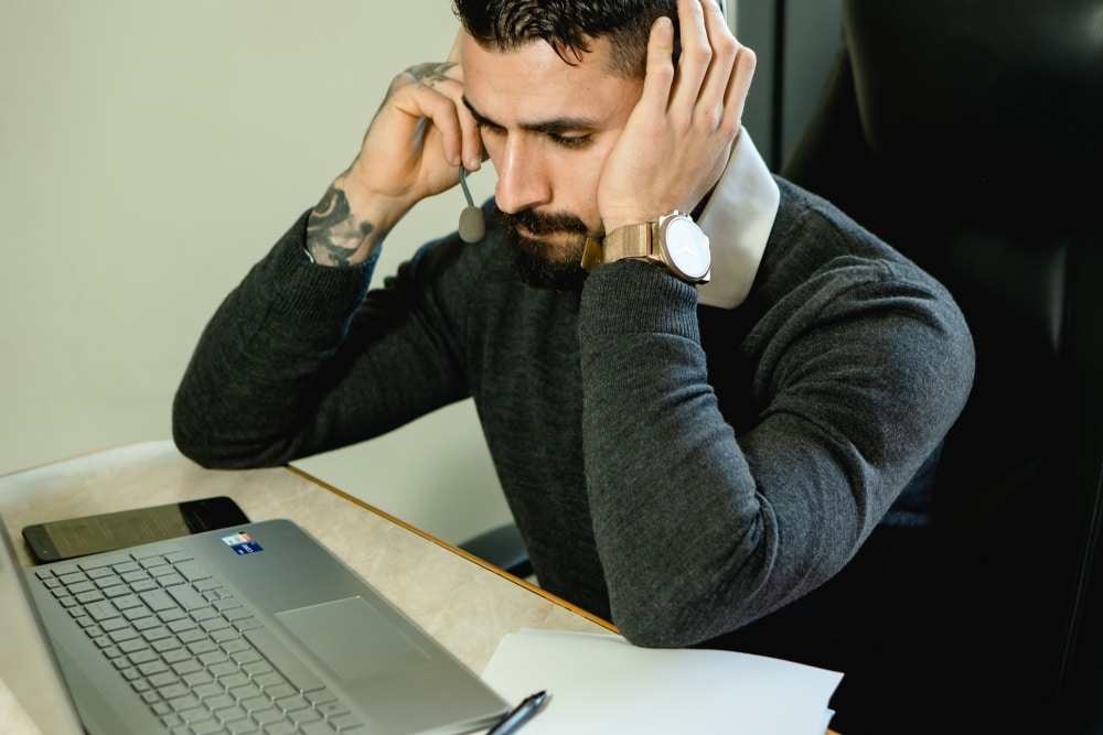 A man at a computer considers how to write the best responses to bad reviews.