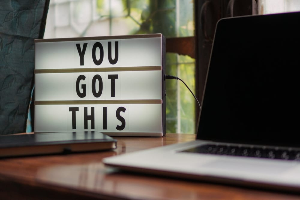 "Sign saying ""you got this"" on a sign, next to laptop on a desk"