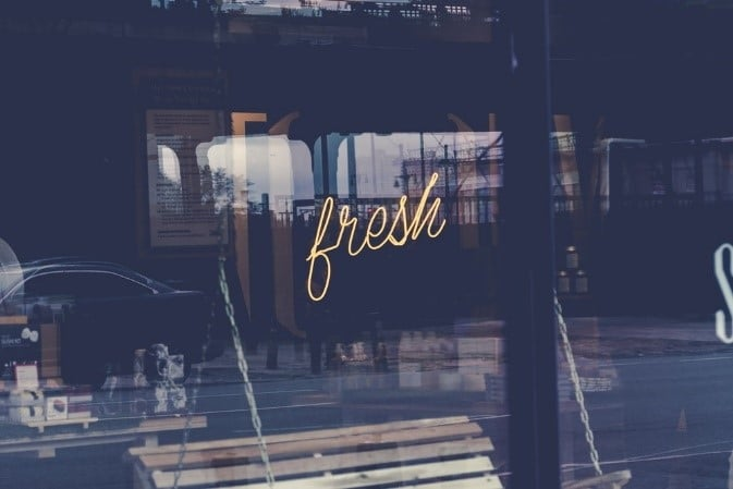 Yellow sign that says the word 'fresh' in a café window.