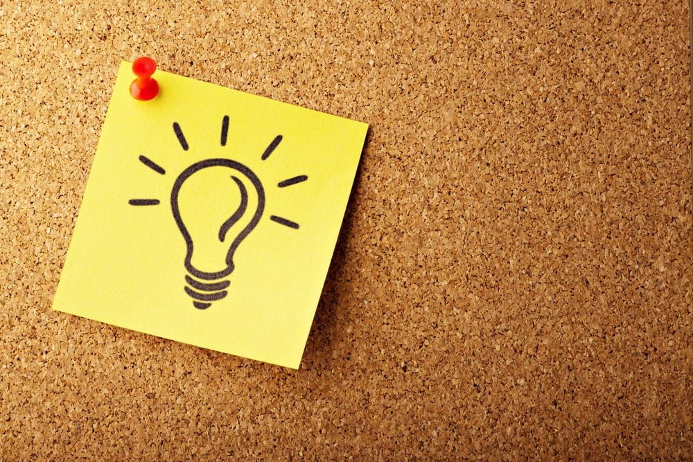 Yellow sticky note with lightbulb drawn on it.