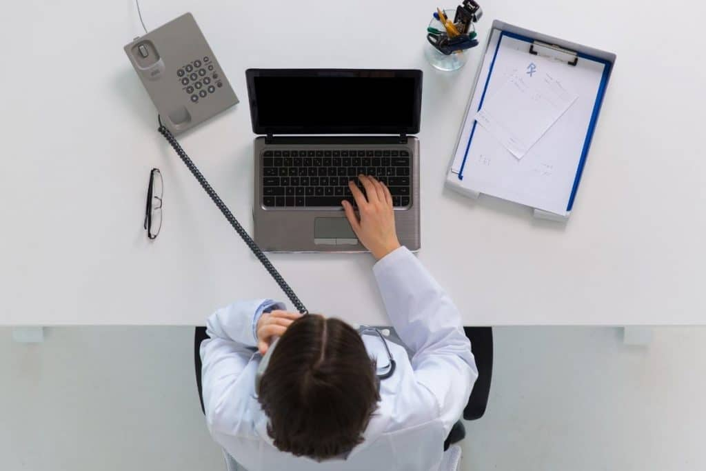 A digital marketer sat at his desk while on the phone to a client. Effective communication is a major benefit of a specialist digital marketing agency.