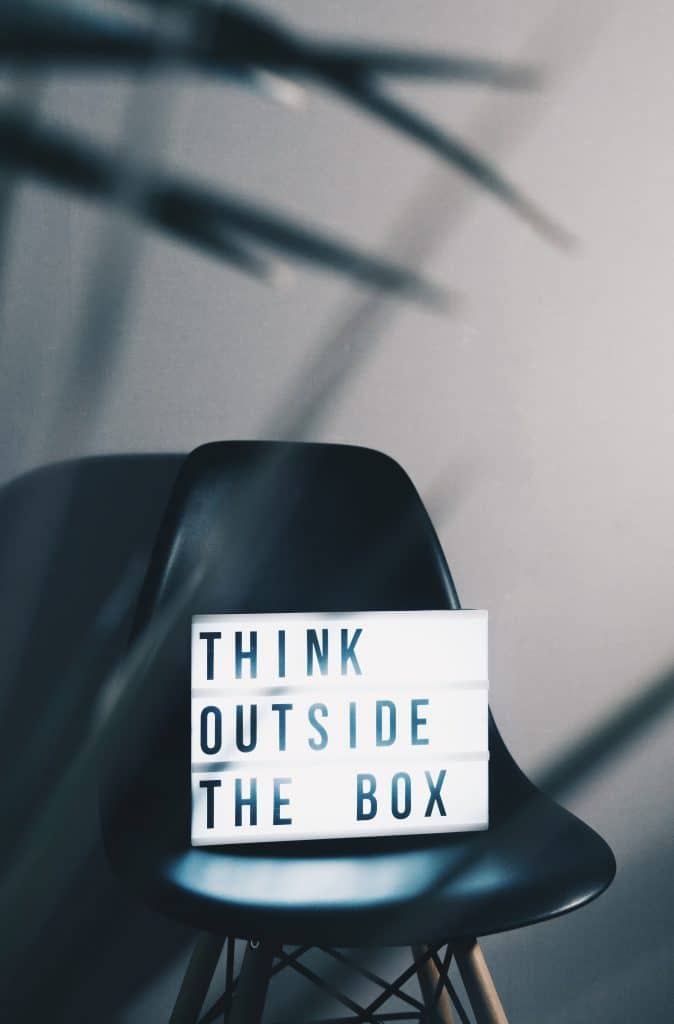 """A Lightbox that Reads """"Think Outside the Box"""" on Top of a Black Chair"""