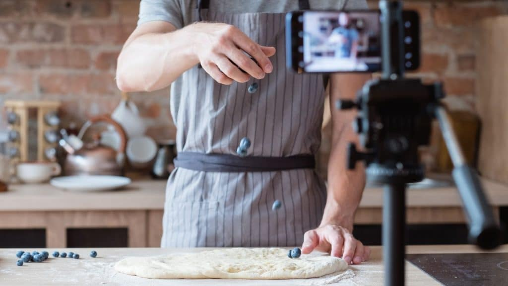 A chef films himself baking using a smartphone and a tripod.