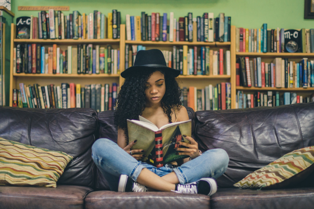 A person on a leather sofa in front of a wall of bookshelves, reading a book.