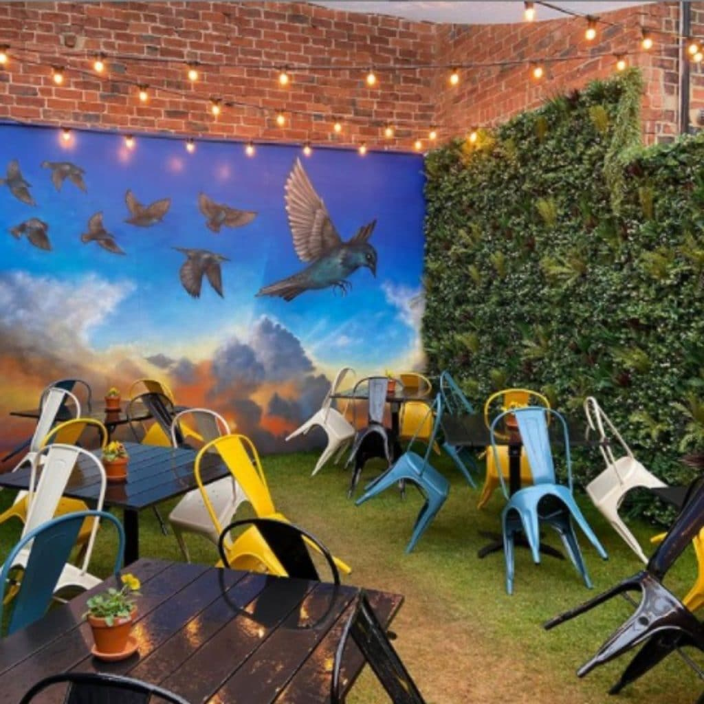 Instagrammable outdoor wall mural of starlings flying in the sunset in Starling bar-cafe, Harrogate