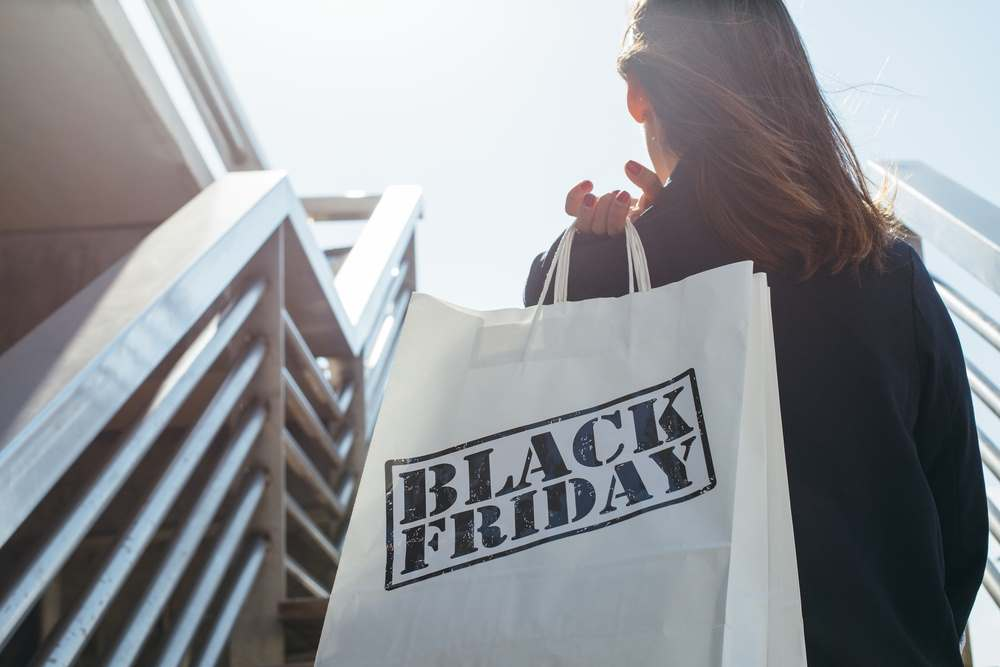 Brunette woman walking up stairs with a white shopping bag over her shoulder. The bag reads Black Friday in bold black letters.